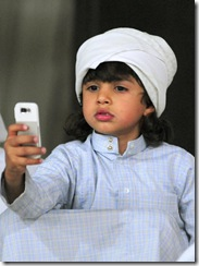 A Saudi child uses his mobile phone to take pictures of colourful roosters during a chicken beauty contest eastern Saudi city of Qatif, on May 02, 2008. AFP PHOTO/STR (Photo credit should read -/AFP/Getty Images)